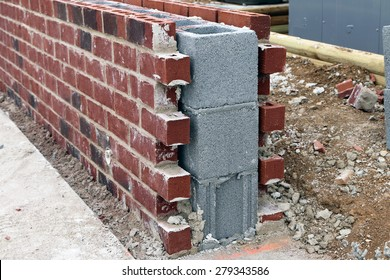 Cement block wall under construction with brick facing for decoration.