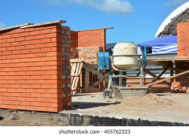 Cement Concrete Mixer on the House Construction Site. Concrete mixer, Concrete blender is a device that homogeneously combines cement, aggregate such as sand or gravel, and water to form concrete.