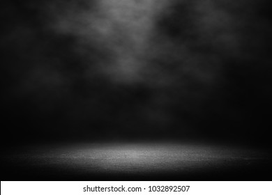 cement floor in dark room with spot light. black background.
