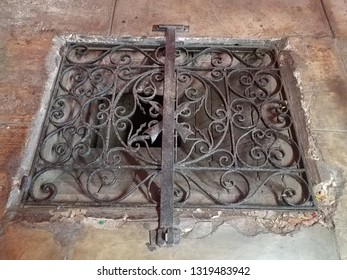 cement floor with locked iron grate covering hole