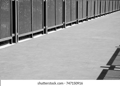 cement gangway and metal rail with shadow - monochrome