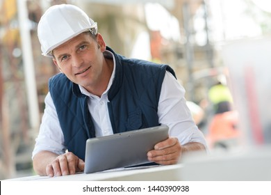 cement manufacturing manager holding tablet