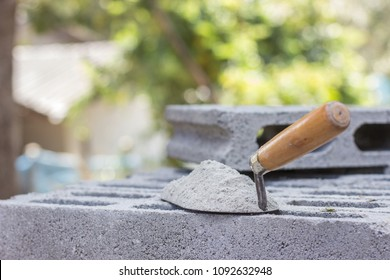 Cement mix or mortar with a trowel put on the brick for construction work.