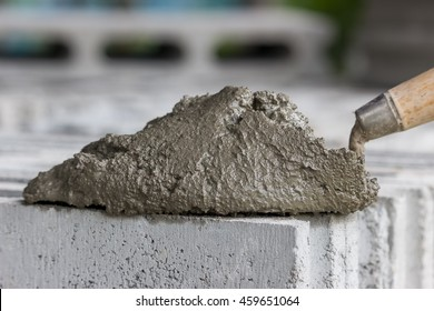 Cement or mortar, Cement mix with a trowel put on the brick for construction work.
