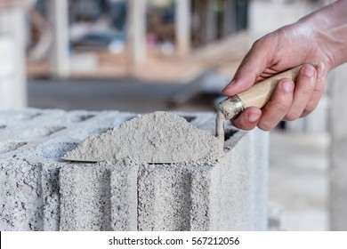 Cement or mortar, Cement powder with a trowel in a hand put on the brick for construction work.