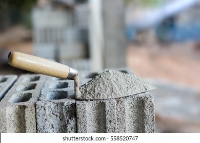 Cement or mortar, Cement powder with a trowel put on the brick for construction work.
