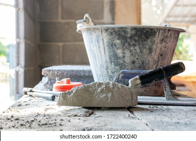 Cement or mortar and trowel with cement powder laid on a wooden plank for construction.