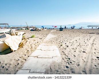 Cement path on public sandy beach with unidentifiable people sunbathing, barks on the left. Beach of Malaga Spain.