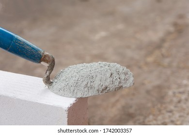 Cement powder or mortar with  trowel put on the Lightweight Concrete brick for construction work.