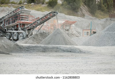 Cement production factory on mining quarry. Conveyor belt of heavy machinery loads stones and gravel.  Industrial background with working gravel crusher
