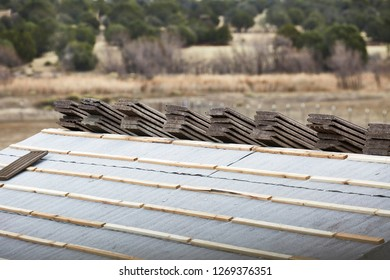 Cement roofing tiles stacked on roof in preparation to lay them
