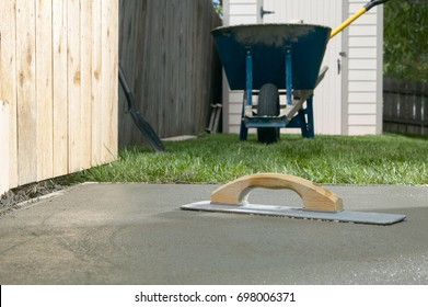 A cement screed resting on a finished concrete slab in backyard, DIY home project themed image.