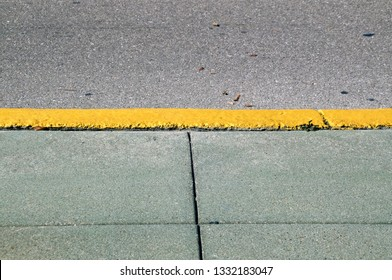 A cement sidewalk with yellow painted curb and part of street on a sunny morning.