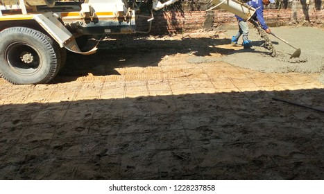 Cement truck is being poured cement into the prepared sand floor while the workers are using the tools to work at the same time.