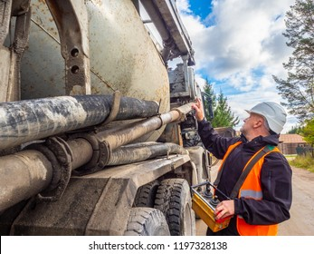 Cement truck. Delivery of cement to the construction site. A man remotely controls the supply of cement.