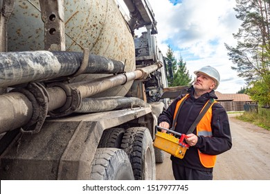 Cement truck. A man controls the flow of concrete. Delivery of concrete to the construction site. Remote control cement supply. Building.