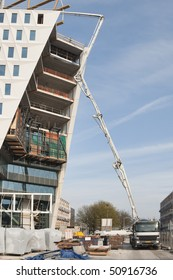 A cement truck with mounted pump is pumping concrete to the top floor of a highrise