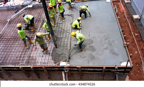 Cement vibrator machine is used immediately after a wet concrete cement pour. Other workers uses squeegee, screed board and trowels to carry out the levelling works.