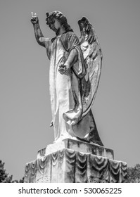 A cemetery angel with her hand raised in the air and looking down over the graves in black and white