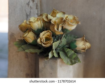 Cemetery, cloth flowers in front of a tomb.