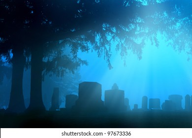 Cemetery in the foggy sunrise with beams or rays of light shining through the trees.