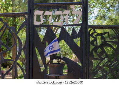"Cemetery gate memorial sign in Israel. written word ""Lezichram"" meaning ""in rememberance of"". Israel flag"