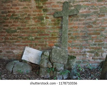 Cemetery, grave. Crucifix and brick wall.