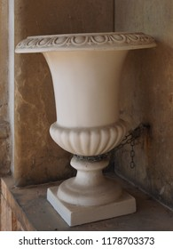 Cemetery, large vase with chain that secures it to the wall.