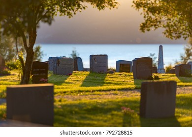 Cemetery in Norway on sunny day with blue water and mountain in background and green grass in foreground