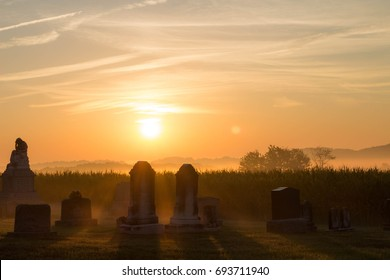 cemetery silhouetted by sunrise and surrounded by light fog