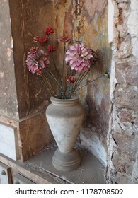 Cemetery, vase with flowers in front of a plaque.