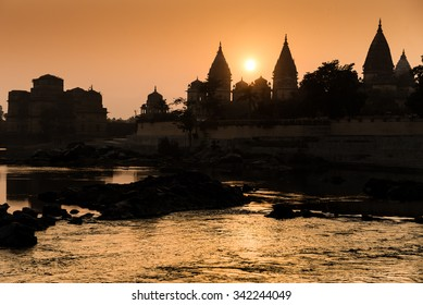 Cenotaphs in silhouette at sunset along the Betwa river, Orchha, Madhya Pradesh state, India.