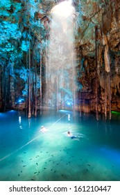 Cenote Dzitnup near Valladolid, Mexico. Couple (blured) swiming in lovely cenote with turquoise waters and large stalactites