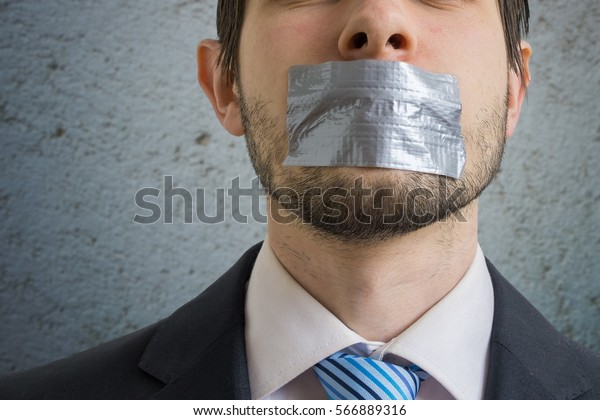 Censorship concept. Man is silenced with adhesive tape on his mouth.