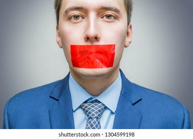 Censorship concept. Man is silenced with red adhesive tape on his mouth