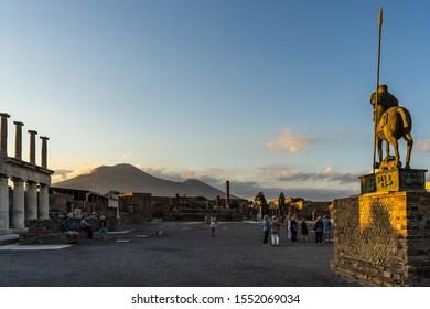 Centaur state  by Igor Mitoraj dominates Pompei Forum at sunset with Mount Vesuvius in the background. Pompeii, Italy, October 2019