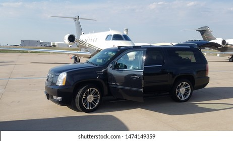 CENTENNIAL, COLORADO- AUGUST 6, 2019: Cadillac Escalade parked by a private jet