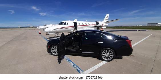CENTENNIAL, COLORADO - MAY 17, 2020: Black limousine parked by a private jet