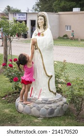 CENTENO, SANTA FE, ARGENTINA - DECEMBER 8, 2013: A devotee child of Mary the Mystical Rose is touching its statue on December 8, 2013 in Centeno city, Santa Fe province, Argentina