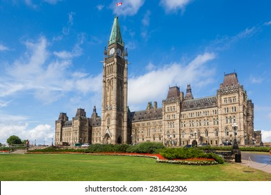The Center Block and the Peace Tower in Parliament Hill, Ottawa, Canada. Center Block is home to the Parliament of Canada. The central green lawn and the red flowers  front the iconic building.