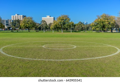 The center circle of a suburban football ground with the goal posts and city skyline of melbourne Australia in the background.