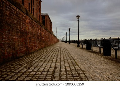 In the center of a cobblestone path on the Liverpool waterfront. The eerie sky fills the sky and a red brick wall aligns the left side of the photo, with the water to the right side.