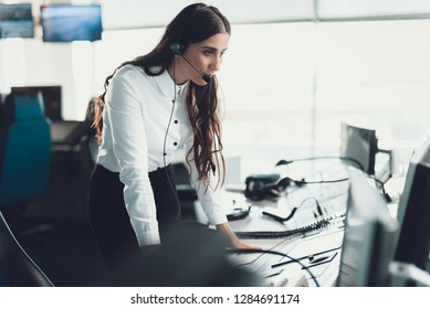 Center of dispatching maintenance. Portrait of young thoughtful woman monitoring information while staying near navigation controller board