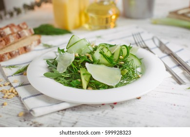 At the center of the frame white plate with a salad of arugula, rocket, avocado, pomegranate seeds, parmesan cheese, spices. Rocket salad on a white background. Horizontal shot. Top view.