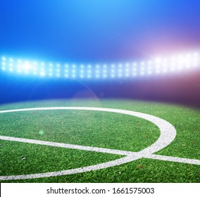 Center of a green football field on a stadium with bright lights and flashes at night