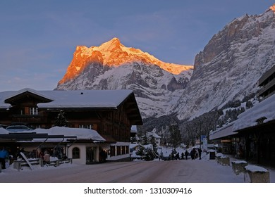 Center of the Grindelwald village with the mountain Wetterhorn at dusk in the background, the street is snow covered in winter, Grindelwald, Bern, Switzerland, Europe