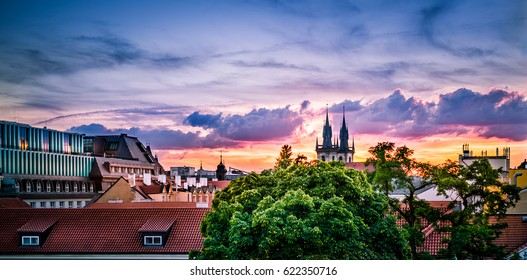 The center of the historic city with view of the rooftops of old houses, church towers and treetops in the glow of warm, colorful sunset with clouds over the horizon.
