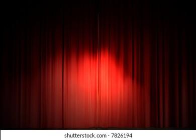Center stage spotlight against a red velvet curtain