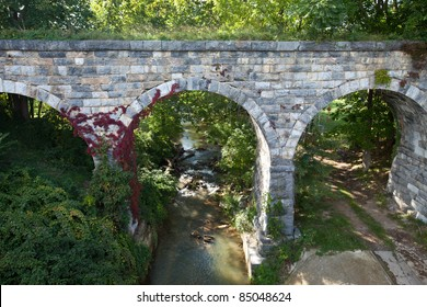 Center view of old stone bridge with red vine built in 1874
