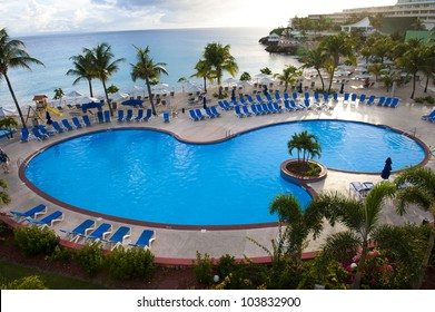 A centered, birds eye view shot of an empty beach resort swimming pool.
